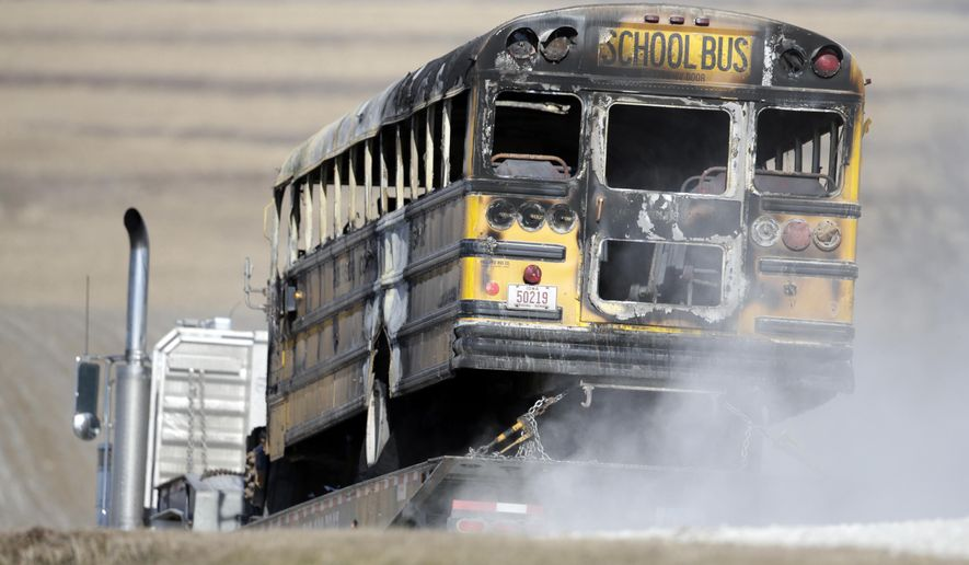 FILE - In this Tuesday, Dec. 12, 2017, file photo, a burned school bus is transported by trailer near Oakland, Iowa. A fire aboard the school bus has killed a student and the bus driver. A western Iowa school district has agreed to pay an undisclosed amount in a settlement to the family of 16-year-old girl who died in the 2017 school bus fire that also killed the 74-year-old bus driver. (AP Photo/Nati Harnik, File)