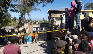 People stand outside the Orphanage of the Church of Bible Understanding where a fire broke out the previous night in the Kenscoff area outside Port-au-Prince, Haiti, Friday, Feb. 14, 2020. A fire swept through this orphanage run by a Pennsylvania-based nonprofit group, killing 13 children, including infants, according to health care workers. (AP Photo/Dieu Nalio Chery)