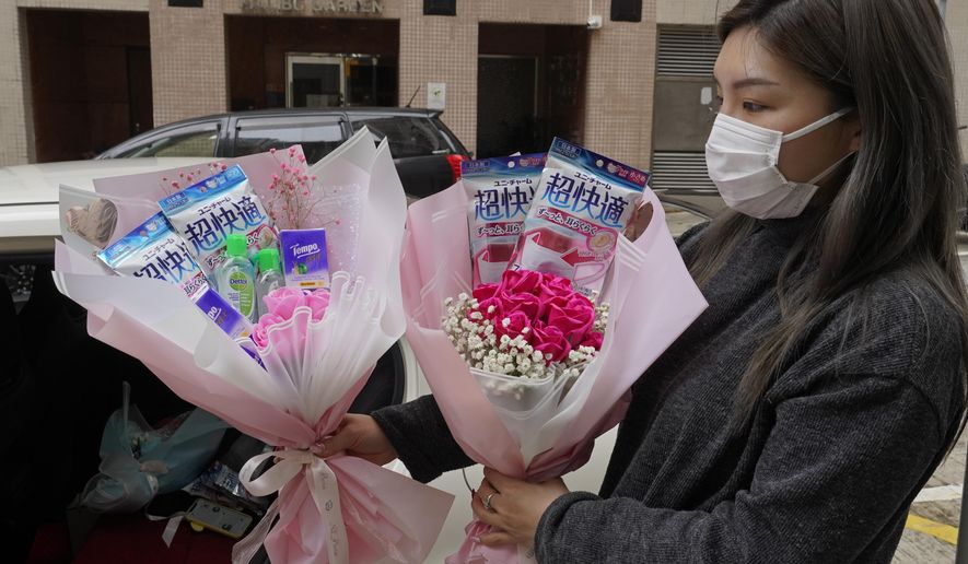Flower shop owner Iris Leung wears her protective face mask as she delivers flowers with masks to customers on Valentine's Day in Hong Kong, Friday, Feb. 14, 2020. China has reported another sharp rise in the number of people infected with a new virus, as the death toll neared 1,400. (AP Photo/Vincent Yu)