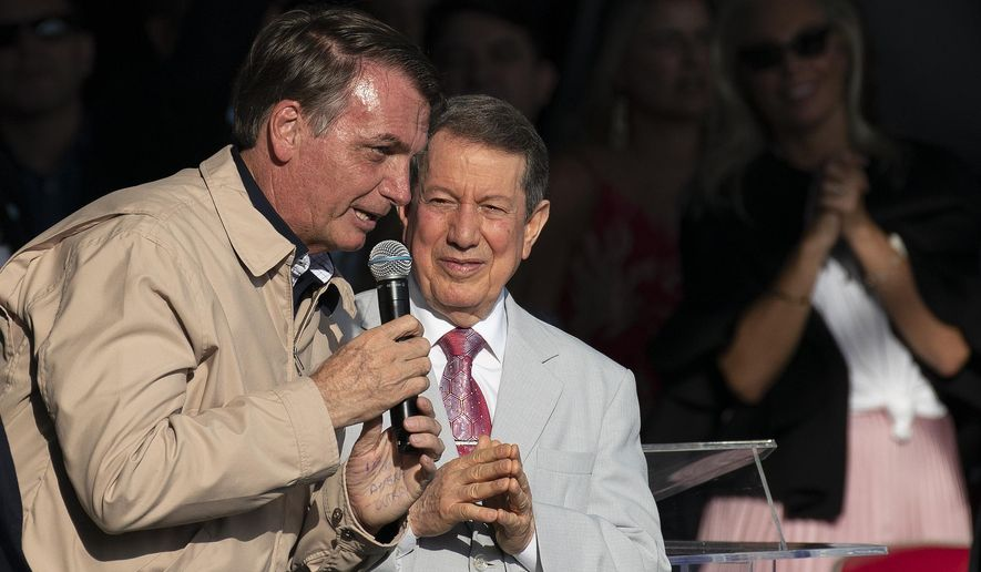 Brazil's President Jair Bolsonaro speaks, accompanied by televangelist R.R. Soares, at an International Grace of God Church event, at Botafogo beach in Rio de Janeiro, Brazil, Saturday, Feb. 15, 2020. Tens of thousands of people gathered to celebrated the 40th anniversary of the evangelical church. (AP Photo/Leo Correa)