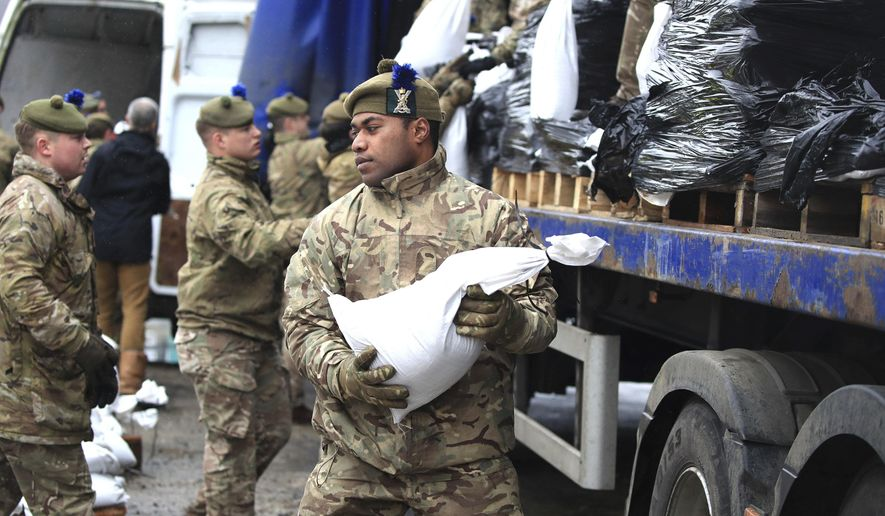 Soldiers from The Highlanders, 4th Battalion, the Royal Regiment of Scotland assist with flood defences as the UK prepares for widespread weather disruption as Storm Dennis approaches, in Mytholmroyd, West Yorkshire, England, Saturday, Feb.15, 2020.  Enormous waves churned across the North Atlantic on Saturday as Britain braces for a second straight weekend of wild winter weather and flooding that's already seen the army deployed to help out residents in northern England. (Danny Lawson/PA via AP)