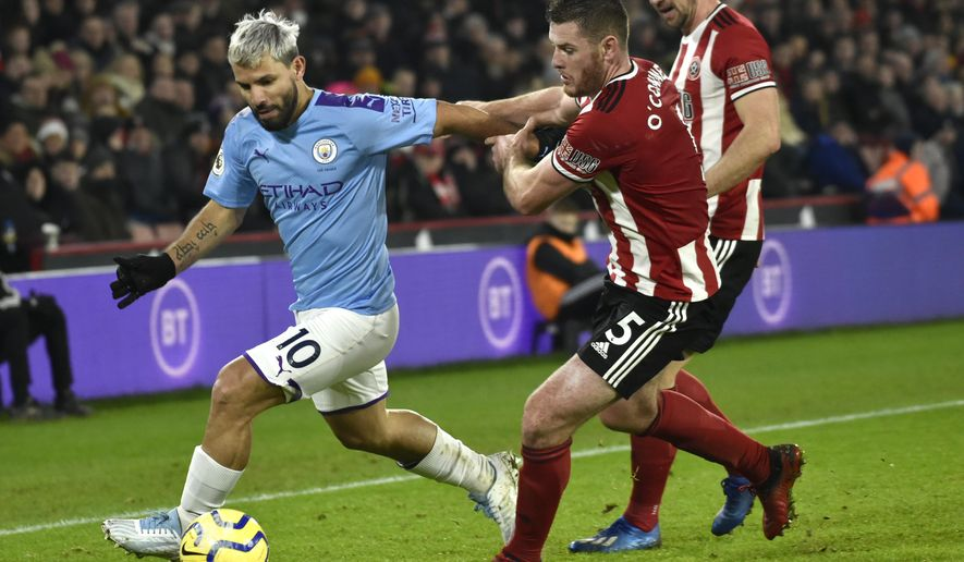 Manchester City's Sergio Aguero, left, and Sheffield United's Jack O'Connell challenge for the ball during the English Premier League soccer match between Sheffield United and Manchester City at Bramall Lane in Sheffield, England, Tuesday, Jan. 21, 2020. (AP Photo/Rui Vieira)