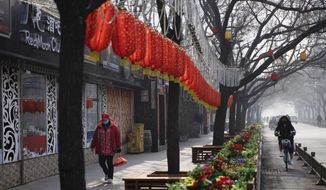 In this photo taken Tuesday, Feb. 11, 2020, a woman walks past Lunar New Year decor and shuttered bars at a retail district in Beijing, China. Millions of Chinese workers and entrepreneurs are bearing the rising costs of an anti-virus campaign that has shut down large sections of the economy. The government has imposed restrictions nationwide that have stalled travel and sales of real estate and autos. (AP Photo/Ng Han Guan)