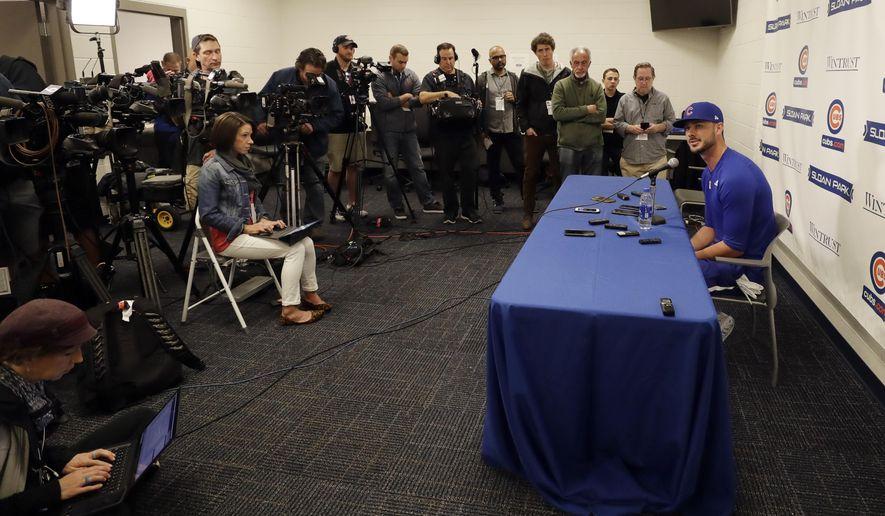 Chicago Cubs third baseman Kris Bryant, right, speaks to reporters during spring training baseball Saturday, Feb. 15, 2020, in Mesa, Ariz. (AP Photo/Gregory Bull)