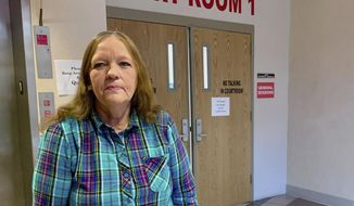 In this Jan. 23, 2020 photo, Susie Duvall, of Jamestown, Tenn., poses outside a courtroom in the Putnam County Courthouse in Cookeville, Tenn. Duvall went to Cookeville Regional Medical Center in September 2018 with confused speech and an aching arm. She stayed a full week and left with a bill that even after insurance, left her to pay more than $9,000. Her arrangement with the court will take more than a decade to pay off.  (Blake Farmer/WPLN via AP)
