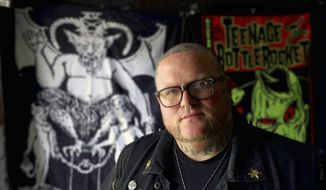 In this Feb. 11, 2014, photo, Chad Sheppard poses for a photo in Columbus, Ga. Sheppard and his wife Chelsea Sheppard are co-owners of Offbeat, an oddities and collectibles store in Columbus. A few strands of Charles Manson's hair, a vintage serial killer board game and a (potentially) haunted last rites kit, are available for viewing in a small museum located in the back of the shop. (Mike Haskey/Ledger-Enquirer via AP)