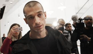 FILE - In this Jan. 10, 2019 file photo, Russian performance artist Pyotr Pavlensky arrives at the Paris courthouse, as he goes on trial after he set fire to the facade of France's central bank in Paris. Pyotr Pavlensky, noted for macabre, politically charged actions reportedly claimed responsibility for the online video posts that apparently prompted Benjamin Griveaux's resignation to become mayor of Paris. (AP Photo/Christophe Ena)