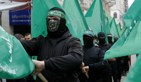"""Masked Hamas militants wave their green flags during a protest against the Mideast plan announced by U.S. President Donald Trump, after the Friday prayer at the main road in Gaza City, Friday, Feb. 14, 2020. Arabic on the headband reads """" a headband with Arabic that reads: """"No God but Allah and Muhammed is his messenger, al-Qassam Brigades"""" (AP Photo/Adel Hana)"""