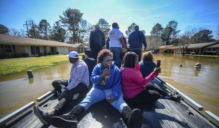 Residents of Canton Club Circle subdivision in Northeast Jackson, Miss., use a boat to get to flooded homes Saturday, Feb. 15, 2020. (Cam Bonelli/Hattiesburg American via AP)