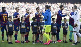 """Barcelona players wearing Ousmane Dembele shirts in support of their seriously injured team mate shake hands with Getafe players in the company of boys and girls of Chinese origin from the Penya Dracs Units Xinesos, the Chinese FC Barcalona supporters club based in Barcelona, wearing a shirt with the message Stronger Together in English and """"Support for China"""" in Chinese. during a Spanish La Liga soccer match between Barcelona and Getafe at the Camp Nou stadium in Barcelona, Spain, Saturday Feb. 15, 2020. (AP Photo/G.Garin)"""