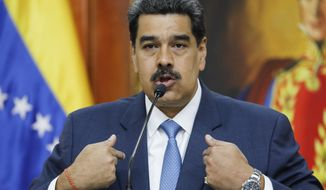 """Venezuelan President Nicolas Maduro gives a press conference at Miraflores presidential palace in Caracas, Venezuela, Friday, Feb. 14, 2020. Maduro said Friday that authorities haven't detained opposition leader Juan Guaido because the courts haven't ordered it, but he warned: """"It will come."""" (AP Photo/Ariana Cubillos)"""