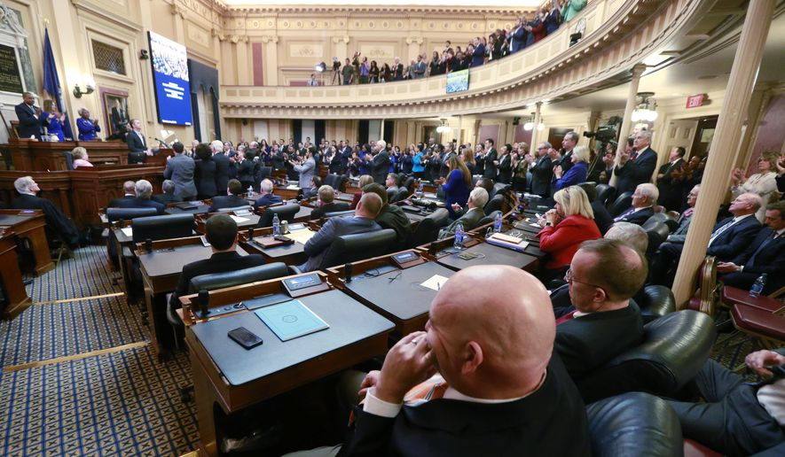 This Wednesday, Jan. 8, 2020, file photo shows House Republicans as they sit in their seats while Democratic lawmakers applaud Virginia Gov. Ralph Northam as he delivers his State of the Commonwealth address before a joint session of the Virginia Assembly at the Virginia state Capitol in Richmond, Va. Northam was talking about his gun control legislation. (AP Photo/Steve Helber) ** FILE **