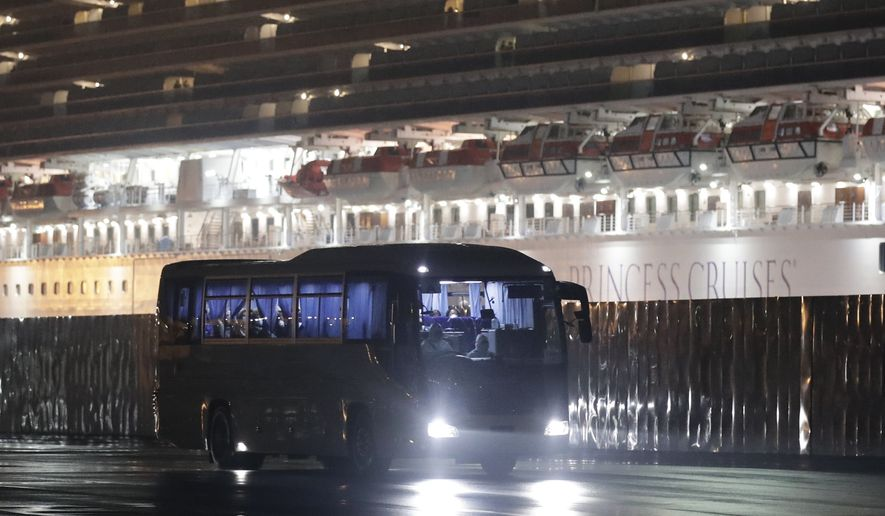 Buses carrying American passengers from the quarantined Diamond Princess cruise ship leave a port in Yokohama, near Tokyo, Monday, Feb. 17, 2020. A group of Americans are cutting short a 14-day quarantine on the Diamond Princess cruise ship in the port of Yokohama, near Tokyo, to be whisked back to America. But they will have to spend another quarantine period at a U.S. military facility to make sure they don't have the new virus that's been sweeping across Asia. (AP Photo/Jae C. Hong)