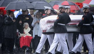 FILE - In this April 6, 2017 file photo provided by the U.S. Army/Arlington National Cemetery, Annie Glenn, seated, widow of John Glenn, watches as members of the U.S. Marine Corps from Marine Barracks Washington carry the casket of her husband during his graveside service at Arlington National Cemetery in Arlington, Va. Glenn turns 100 on Feb. 17, 2020.    (U.S. Army photo by Rachel Larue/Arlington National Cemetery via AP)