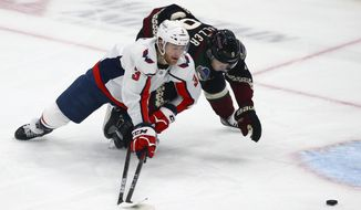 Washington Capitals defenseman Nick Jensen (3) and Arizona Coyotes right wing Clayton Keller, right, battle for the puck during the first period of an NHL hockey game Saturday, Feb. 15, 2020, in Glendale, Ariz. (AP Photo/Ross D. Franklin)