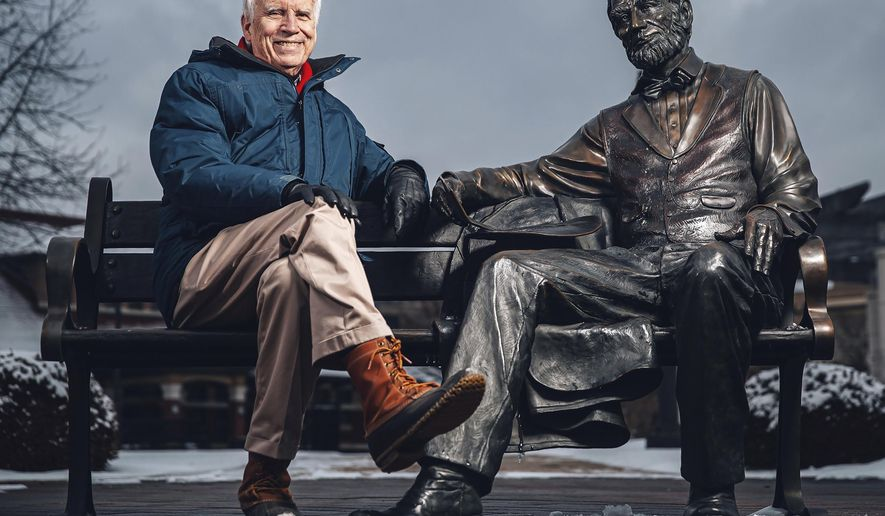 In this Feb. 6, 2020 photo, Michael Burlingame, a Naomi B. Lynn Distinguished Chair in Lincoln Studies at the University of Illinois Springfield, with the sculpture of Abraham Lincoln sculpted by Colorado artist Mark Lundeen that depicts Lincoln relaxing on a bench with a copy of his Second Inaugural Address in his hand in Springfield, Ill. (/The State Journal-Register via AP)/The State Journal-Register via AP)