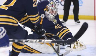 Buffalo Sabres goalie Carter Hutton (40) covers the puck during the first period of an NHL hockey game against the Toronto Maple Leafs, Sunday, Feb. 16, 2020, in Buffalo, N.Y. (AP Photo/Jeffrey T. Barnes)