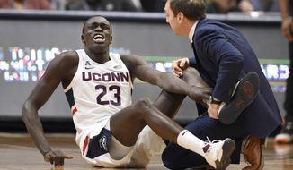 Connecticut's Akok Akok (23) reacts while tended to by head trainer James Doran in the first half of an NCAA college basketball game against Memphis, Sunday, Feb. 16, 2020, in Hartford, Conn. (AP Photo/Jessica Hill)