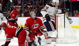 Edmonton Oilers' Leon Draisaitl (29) reacts to his goal as he skates past Carolina Hurricanes' Jaccob Slavin (74), Trevor van Riemsdyk (57) and goaltender James Reimer (47) during the first period of an NHL hockey game in Raleigh, N.C., Sunday, Feb. 16, 2020. (AP Photo/Karl B DeBlaker)
