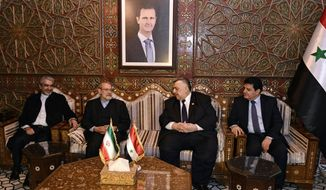 In this photo released by the Syrian official news agency SANA, Speaker of the People's Council of Syria Hammouda Sabbagh, center right, receives Iran's Parliament Speaker Ali Larijani, second left, on his arrival to the airport, in the Syrian capital Damascus, Sunday, Feb. 16, 2020. (SANA via AP)