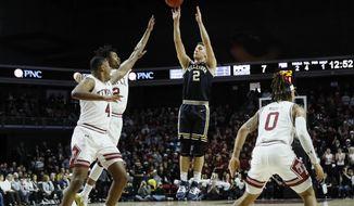 Villanova's Collin Gillespie (2) goes up to shoot past Temple's J.P. Moorman II (4), Monty Scott (2) and Alani Moore II (0) during the first half of an NCAA college basketball game, Sunday, Feb. 16, 2020, in Philadelphia. (AP Photo/Matt Slocum)