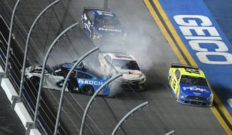 Denny Hamlin (11) squeezes between Ryan Newman (6) and Ryan Blaney (12) along the front stretch to win the NASCAR Daytona 500 auto race at Daytona International Speedway, Monday, Feb. 17, 2020, in Daytona Beach, Fla. (AP Photo/Phelan M. Ebenhack)