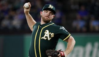FILE - In this Sept. 14, 2019, file photo, Oakland Athletics relief pitcher Liam Hendriks works against the Texas Rangers during a baseball game in Arlington, Texas. Hendriks had to help somehow when fires ravaged his homeland in Australia this winter. He briefly got home to Perth but mostly campaigned on social media from a world away to generate awareness and support for Red Cross Australia. (AP Photo/Tony Gutierrez, File)
