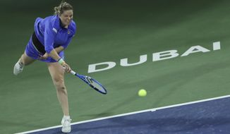 Belgium's Kim Clijsters serves to Spain's Gabrine Muguruza during a match of the Dubai Duty Free Tennis Championship in Dubai, United Arab Emirates, Monday, Feb. 17, 2020. (AP Photo/Kamran Jebreili)