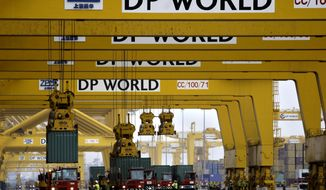 FILE - In this Feb. 8, 2009 file photo, cranes off load containers at the Jebel Ali port terminal 2, in Dubai, United Arab Emirates. Port operator DP World said Monday, Feb. 17, 2020, that it will delist from the Nasdaq Dubai stock exchange, returning the company to full state-ownership in a move that will help the Dubai government's investment company repay more than $5 billion to banks. (AP Photo/Kamran Jebreili, File)