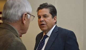 New Mexico Sen. Joseph Cervantes, D-Las Cruces, talks to a staffer on Monday, Feb. 17, 2020, at the Capitol in Santa Fe, N.M. (AP Photo/Russell Contreras)