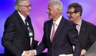 FILE - In this March 1, 2012 file photo, former President Bill Clinton shakes hands with Owen Bieber, left, with United Auto Workers union (UAW), at the 2012 UAW National Community†Action Program Conference, at the Marriott Wardman Park Hotel, in Washington.  Bieber, who led the United Auto Workers union from the auto industry's dark days of the early 1980s to the prosperity of the mid-1990s, has died. He was 90.(AP Photo/Jacquelyn Martin, File)