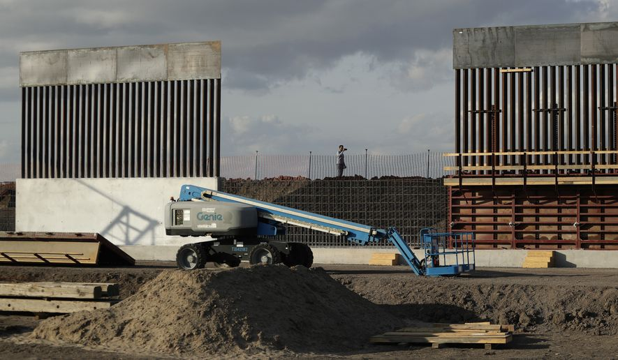 In this Nov. 7, 2019, photo, the first panels of levee border wall are seen at a construction site along the U.S.-Mexico border, in Donna, Texas. The Trump administration said Tuesday, Feb. 18, 2020, that it will waive federal contracting laws to speed construction of the border wall with Mexico. (AP Photo/Eric Gay) **FILE**