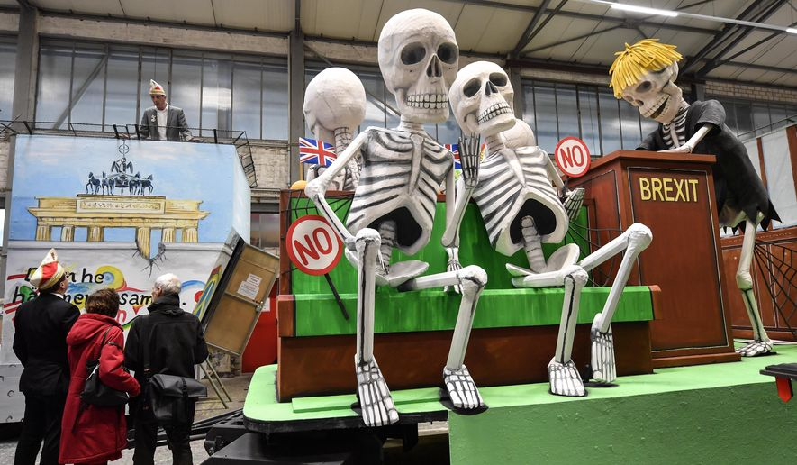 A satiric carnival float depicting the Brexit and British members of Parliament as skeletons, is watched by revellers during a preview in a hall in Cologne, Germany, Tuesday, Feb. 18, 2020. The traditional carnival parades on Rosemonday make fun of politics and are watched by hundreds of thousands in the streets of Cologne, Duesseldorf and Mainz. (AP Photo/Martin Meissner)