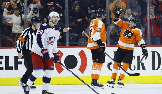 Philadelphia Flyers' Kevin Hayes (13) and Ivan Provorov (9) celebrate past Columbus Blue Jackets' Oliver Bjorkstrand (28) after a goal by Hayes during the first period of an NHL hockey game, Tuesday, Feb. 18, 2020, in Philadelphia. (AP Photo/Matt Slocum)
