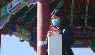 A woman wearing a face mask stands at a pagoda in Ritan Park in Beijing, Tuesday, Feb. 18, 2020. A hospital director who helped lead the fight against China's new virus has become one of its victims. His death comes as authorities are cautiously cheering a reduction in the number of new daily cases and deaths, along with the results of a study showing most people who contract the virus experience only mild symptoms. (AP Photo/Sam McNeil)