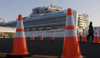 In this Feb. 13, 2020, file photo, a security guard stands near the quarantined Diamond Princess cruise ship in Yokohama, near Tokyo. After 14 days, an extraordinary quarantine of the Diamond Princess cruise ship ends Wednesday, Feb. 19, 2020, with thousands of passengers and crew set to disembark over the next several days in the port of Yokohama. (AP Photo/Jae C. Hong, File)