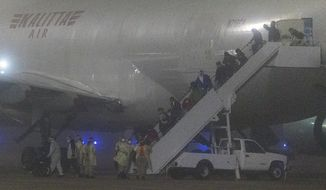 American passengers evacuated from a cruise ship in Japan disembark from a Kalitta Air flight at Kelly Field, early Monday, Feb. 17, 2020 in San Antonio, Texas.  The U.S. said it arranged the evacuation because people on the Diamond Princess were at a high risk of exposure to the new virus that's been spreading in Asia. For the departing Americans, the evacuation cuts short a 14-day quarantine that began aboard the cruise ship Feb. 5.   (William Luther /The San Antonio Express-News via AP)