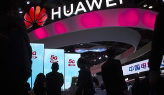 FILE - In this Oct. 31, 2019, file photo, attendees walk past a display for 5G services from Chinese technology firm Huawei at the PT Expo in Beijing. The Trump administration is stepping up pressure on European allies to ban Chinese tech firm Huawei from supplying next-generation mobile networks, with more officials visiting this week to press the case. (AP Photo/Mark Schiefelbein, File)