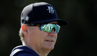 Seattle Mariners manager Scott Servais watches spring training baseball practice Thursday, Feb. 13, 2020, in Peoria, Ariz. (AP Photo/Charlie Riedel)