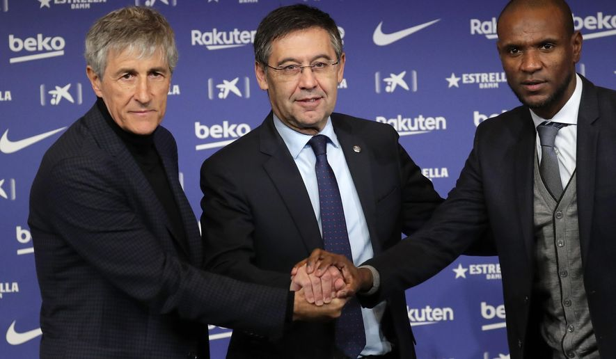Soccer coach Quique Setien poses with FC Barcelona's President Josep Maria Bartomeu, center, and director of football Eric Abidal, right, while being officially introduced as the club's new coach at the Camp Nou stadium in Barcelona, Spain, Tuesday, Jan. 14, 2020. Barcelona made a rare coaching change midway through the season, replacing Ernesto Valverde with former Real Betis manager Quique Setien on Monday. (AP Photo/Emilio Morenatti)