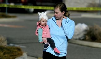 Mary Boyle, 34, and her daughter Adie, 11 months, were evacuated from the Walmart store in Broomfield, Colo. on Tuesday, Feb. 18, 2020. A man and woman exchanged gunfire inside the suburban Denver Walmart, panicking shoppers and triggering a swarming police response, police said. (Hyoung Chang/The Denver Post via AP)