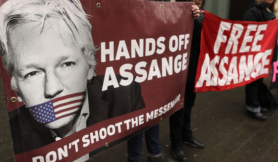 Demonstrators hold banners outside Westminster Magistrates Court in London, Wednesday, Feb. 19, 2020. A case-management hearing regarding Julian Assange will be heard at the court Wednesday. (AP Photo/Kirsty Wigglesworth)