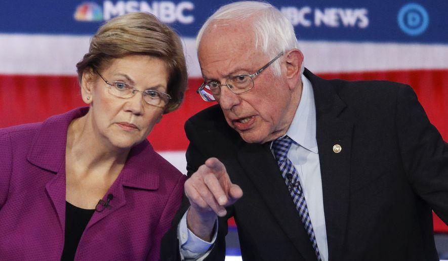 Democratic presidential candidates, Sen. Elizabeth Warren, D-Mass., left, and Sen. Bernie Sanders, I-Vt., talk during a Democratic presidential primary debate Wednesday, Feb. 19, 2020, in Las Vegas, hosted by NBC News and MSNBC. (AP Photo/John Locher)