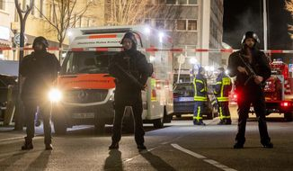 Police guard the scenery in front of a restaurant in central Hanau, Germany Thursday, Feb. 20, 2020. German police say several people were shot to death in the city of Hanau on Wednesday evening. (AP Photo/Michael Probst)