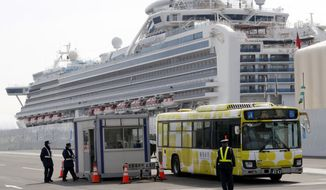 A bus carrying passengers from the quarantined Diamond Princess cruise ship leaves a port in Yokohama, near Tokyo, Thursday, Feb. 20, 2020. Passengers tested negative for COVID-19 started disembarking since Wednesday. (AP Photo/Eugene Hoshiko)
