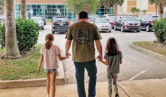 This photo provided by Roush Racing shows NASCAR driver Ryan Newman and his daughters, Brooklyn Sage, left, and Ashlyn Olivia, leaving Halifax Medical Center, Wednesday, Feb. 19, 2020 in Daytona Beach, Fla. Ryan Newman was released from a Florida hospital on Wednesday, about 42 hours after his frightening crash on the final lap of the Daytona 500.(Roush Racing via AP)