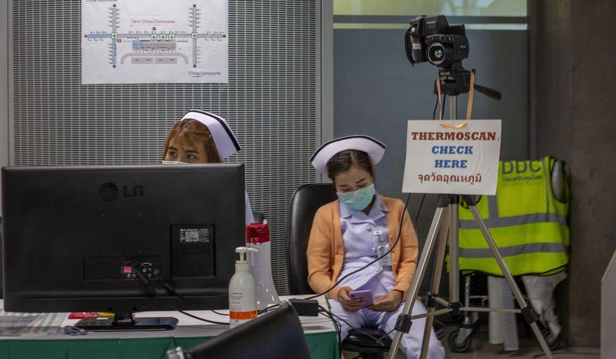 In this Tuesday, Feb. 18, 2020, photo, Thai public health officers operate a health checkpoint with thermo scan, targeting to pick people traveling with fever, a symptom of COVID-19 at Suvarnabhumi International airport in Bangkok, Thailand. Thai Public Health Ministry on Monday, Feb 17, 2020, informed Thais to reschedule their visits to Japan and Singapore citing the rising number of people infected by new coronavirus in those two countries. (AP Photo/Gemunu Amarasinghe)