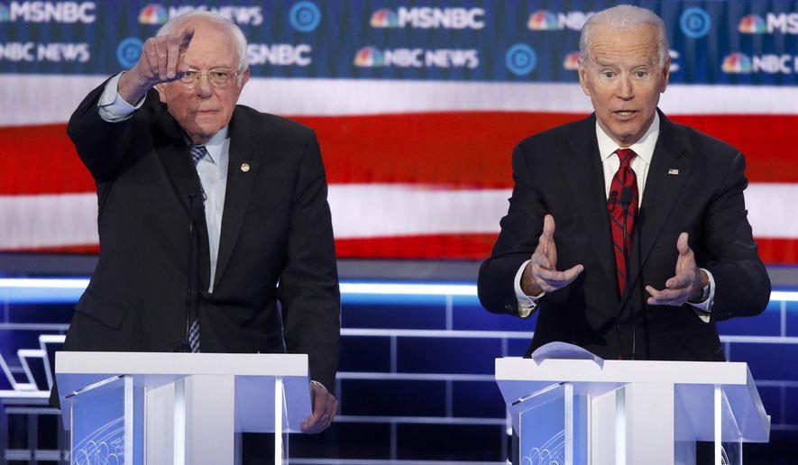 Democratic presidential candidates, Sen. Bernie Sanders, I-Vt., left, and former Vice President Joe Biden gesture during a Democratic presidential primary debate Wednesday, Feb. 19, 2020, in Las Vegas, hosted by NBC News and MSNBC. (AP Photo/John Locher)