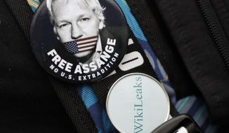 Badges worn by a demonstrator outside Westminster Magistrates Court in London, Wednesday, Feb. 19, 2020. A case-management hearing regarding Julian Assange will be heard at the court Wednesday. It comes just five days before the extradition hearing beginning Feb. 24, at Woolwich Crown Court, in which both Julian Assange and the broader issues of press freedom will be at stake. (AP Photo/Kirsty Wigglesworth)