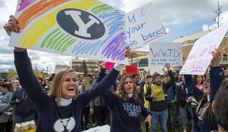 In this April 12, 2019, file photo, Sidney Draughon holds a sign as she takes part in a protest in Provo, Utah, against how the Brigham Young University Honor Code Office investigates and disciplines students. Brigham Young University in Utah has revised its strict code of conduct to strip a rule that banned any behavior that reflected 'homosexual feelings' which LGBTQ students and their allies felt created an unfair double standard not imposed on heterosexual couples. On June 16, 2021, Education Secretary Miguel Cardona announced his agency will interpret Title IX federal legislation to protect LGBT students from discrimination based on sexual orientation or gender identity, a reversal of policy from the Trump administration and a move which critics fear could endanger religious schools. (Rick Egan/The Salt Lake Tribune via AP, File)